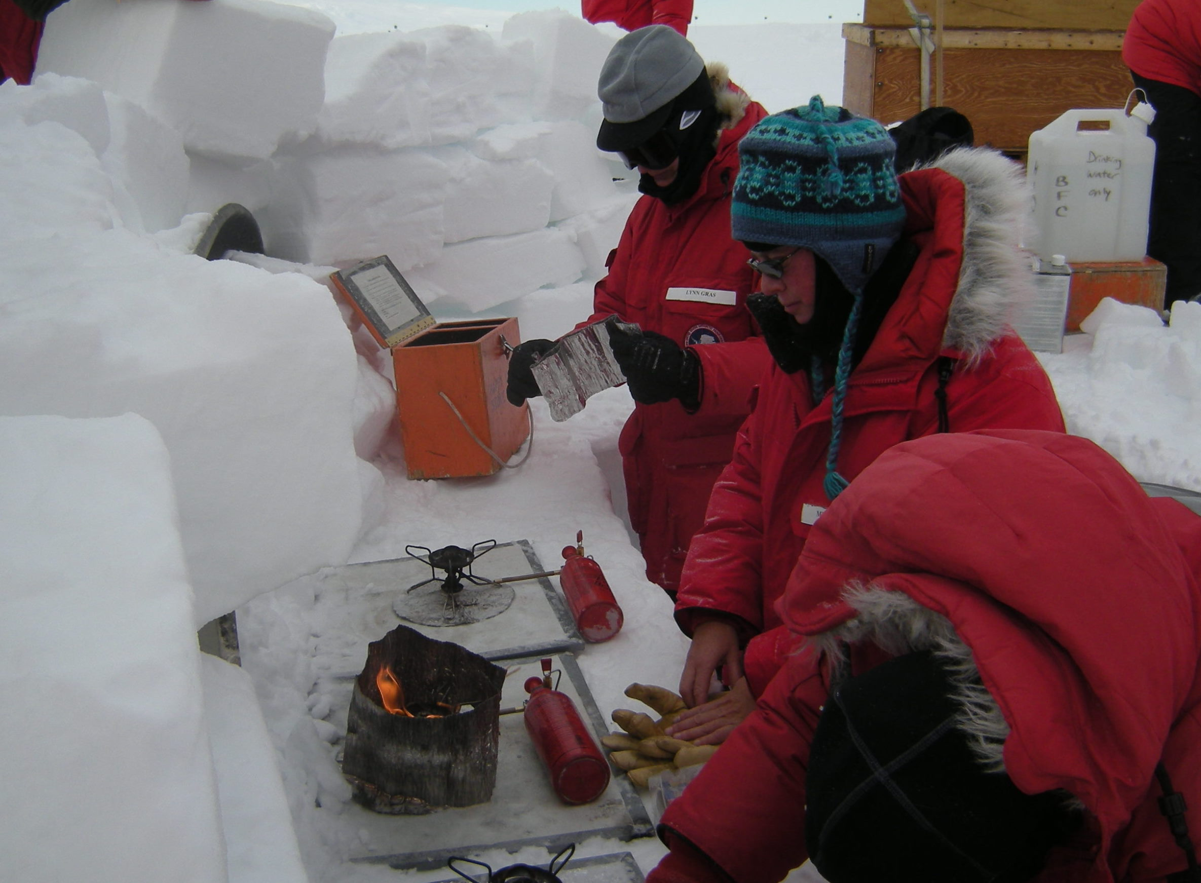 Michelle fires up a stove in the snow galley